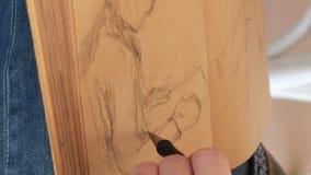 El artista gráfico dibuja el manual de las ilustraciones de la imagen del bosquejo almacen de metraje de vídeo