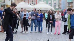 El artista hace el dinero en el instrumento musical, juegos del hombre del violinista delante de una muchedumbre de gente en la c