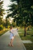 El artista hermoso de la muchacha se est? colocando en el parque y est? sosteniendo la paleta con las pinturas imagenes de archivo