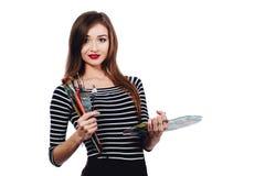 El artista hermoso lindo de la muchacha que sostiene una paleta y un cepillo en el proceso dibuja la inspiración Fondo blanco, ai Imagen de archivo