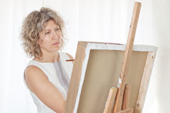 El artista hermoso pinta un cuadro. Imagenes de archivo