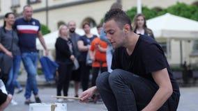 El artista joven de la calle se realiza en un cubo y platos delante de la audiencia de gente