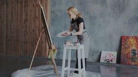 El artista joven de sexo femenino de la pintura en un espacio de trabajo atmosférico con las ventanas panorámicas pintó imágenes