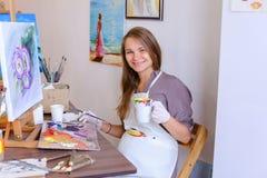 El artista lindo Holds Brush de la muchacha a disposición y extrae, bebe de la taza, Imagen de archivo libre de regalías