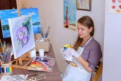 El artista lindo Holds Brush de la muchacha a disposición y extrae, bebe de la taza, Imagenes de archivo