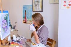 El artista lindo Holds Brush de la muchacha a disposición y extrae, bebe de la taza, Fotos de archivo