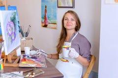 El artista lindo Holds Brush de la muchacha a disposición y extrae, bebe de la taza, Fotos de archivo libres de regalías