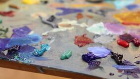 El artista mezcla la pintura en la paleta, pintura mezclada cepillo en la paleta, pintura al óleo del arte del color de la mezcla almacen de metraje de vídeo
