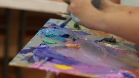 El artista mezcla la pintura en la paleta, pintura mezclada cepillo en la paleta, pintura al óleo del arte del color de la mezcla almacen de video