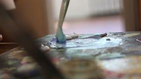 El artista mezcla la pintura en la paleta, pintura mezclada cepillo en la paleta, pintura al óleo del arte del color de la mezcla metrajes