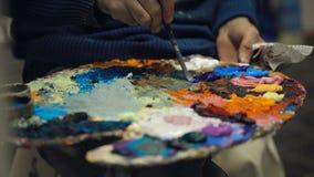 El artista mezcla las pinturas de aceite en la plataforma con diversos colores