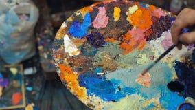 El artista mezcla las pinturas de aceite en la plataforma con diversos colores almacen de metraje de vídeo