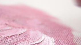 El artista pinta las flores rosadas en la lona con sus fingeres, primer metrajes