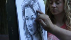 El artista pinta un retrato de una muchacha en el parque almacen de video