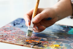 el artista pinta una imagen de la brocha del aceite disponible con la paleta foto de archivo
