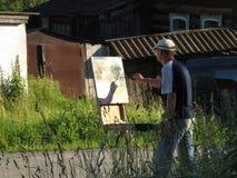 El artista pinta una imagen de las casas viejas del pueblo Fotografía de archivo