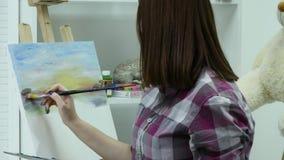 El artista pinta a una mujer en lona y mancha un cepillo amplio La lona se coloca en el caballete El artista dibuja en el caballe almacen de video
