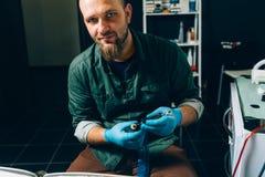 El artista principal del tatuaje prepara las herramientas para tatuar fotos de archivo libres de regalías