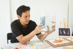 El artista que mira a los pescados rueda para su inspiración a la pintura imagen de archivo libre de regalías