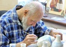 El artista que pinta las botellas de cerámica Fotos de archivo