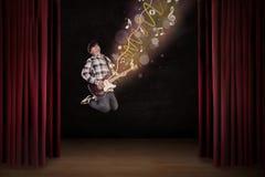 El artista que salta con la guitarra y las notas musicales Imagen de archivo