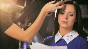 El artista rubio de la muchacha hace maquillaje para anclar con los cosméticos Desheli metrajes