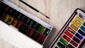 El artista se está preparando para dibujar Abre las cajas, por con las pinturas de la acuarela llegan a ser eventual adicto Manos metrajes