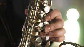 El artista toca el saxof?n Los fingeres pulsan las teclas del saxof?n metrajes