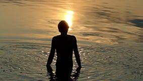 El Arty Sunny Path en un agua de río y un hombre lanza el agua en él almacen de video
