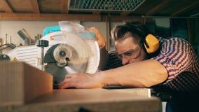 El aserrar de madera realizado por un carpintero de sexo masculino almacen de metraje de vídeo