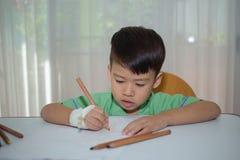 El asiático 3 años embroma el dibujo en el paoer blanco con el lápiz del color al re Imágenes de archivo libres de regalías