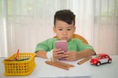 El asiático 3 años embroma el teléfono móvil y el dibujo del juego con penci del color Foto de archivo