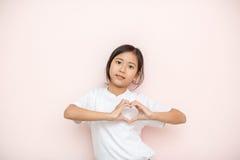 El asiático bronceó el retrato del niño de la muchacha de la piel sobre fondo rosado de la pared, Fotos de archivo
