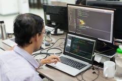 El asiático externaliza el desarrollador de software que mira la pantalla que se sienta el escritorio fotos de archivo