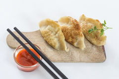 El asiático frió las bolas de masa hervida Gyoza, adornado con la salsa y el perejil Fotos de archivo