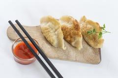 El asiático frió las bolas de masa hervida Gyoza, adornado con la salsa y el perejil Fotografía de archivo libre de regalías