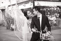 El asiático romántico nuevo-se casa montar una bicicleta fotos de archivo libres de regalías