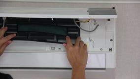 El asiático sirve el filtro del parte movible de la mano en la condición y el cierre del aire la tapa después de limpiar metrajes