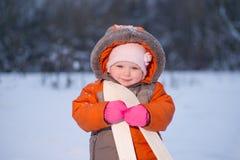 El asimiento adorable del bebé embroma el esquí en manos en parque Imágenes de archivo libres de regalías