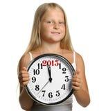 El asimiento de la muchacha en manos un reloj grande Imagen de archivo