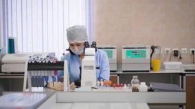 El asistente de investigación femenino en azul friega, máscara protectora, casquillo y los guantes sentándose en el examen del la metrajes