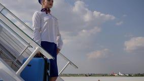 El asistente de vuelo atractivo en escalera movible guarda el bolso del viaje en el cielo azul del fondo y la mirada en distancia metrajes