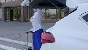 El asistente de vuelo en uniforme del azul guarda el bolso del viaje cerca de avto en aeropuerto del fondo almacen de video