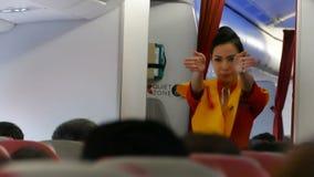 El asistente de vuelo de sexo femenino no identificado en aeroplano explica reglas sobre seguridad durante saca almacen de metraje de vídeo