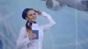 El asistente de vuelo sostiene el pasaporte disponible con los boletos y los saludos en la cámara en fondo azul almacen de metraje de vídeo