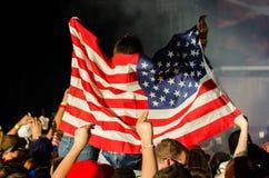 El asistente del concierto de EDM aumenta la bandera americana Imagen de archivo libre de regalías