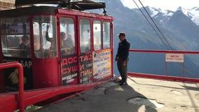 El asistente resuelve la elevación aérea con los visitantes en el centro turístico de Dombay almacen de metraje de vídeo