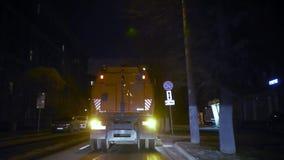 El aspirador del coche va adelante y limpia la calle en la noche delante de la cámara y se aleja almacen de video