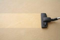El aspirador limpia la alfombra Fotografía de archivo libre de regalías