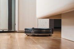 el aspirador negro del robot corre debajo de cama en piso laminado en dormitorio Economía doméstica elegante moderna de la tecnol imagen de archivo libre de regalías